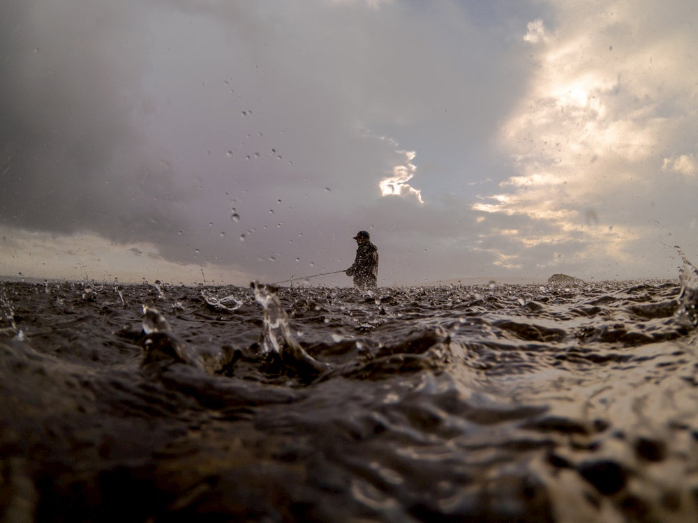 Fly fisherman in puget sound during a rain storm.