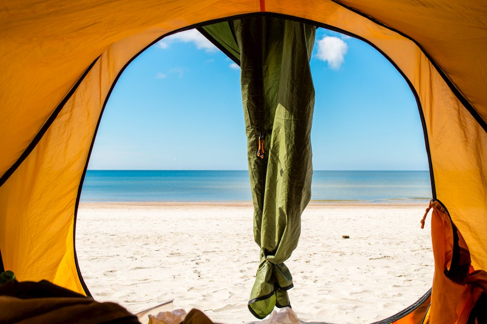 Tent on a beach beside the ocean.