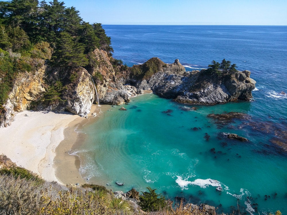 a tide pool in big sur with a waterfall into the ocean