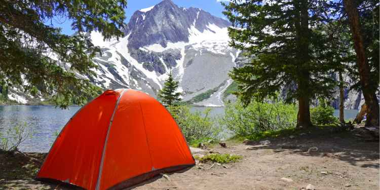 a red tent set up neat a lake with a mountain in the background in colorado