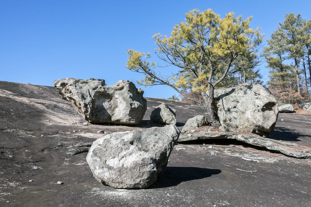granite stones rest on an outcropping near trees on a mountain
