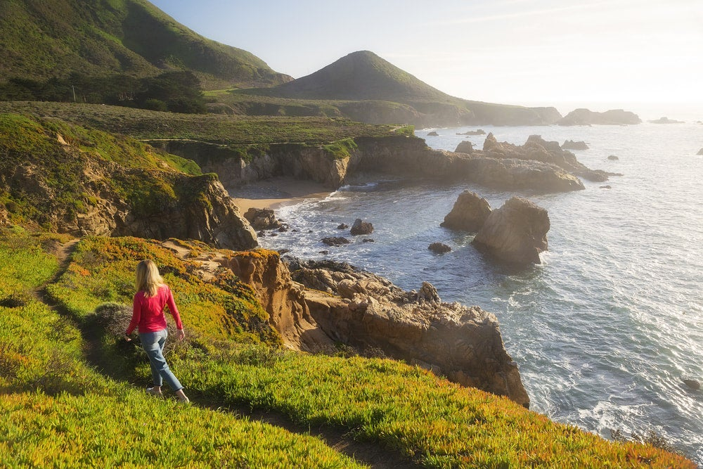 a woman hiking along a path on the coast of big sur