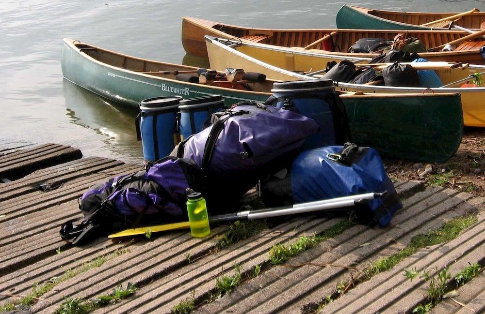 a row of boats near canoe camping gear on the shore of a lake