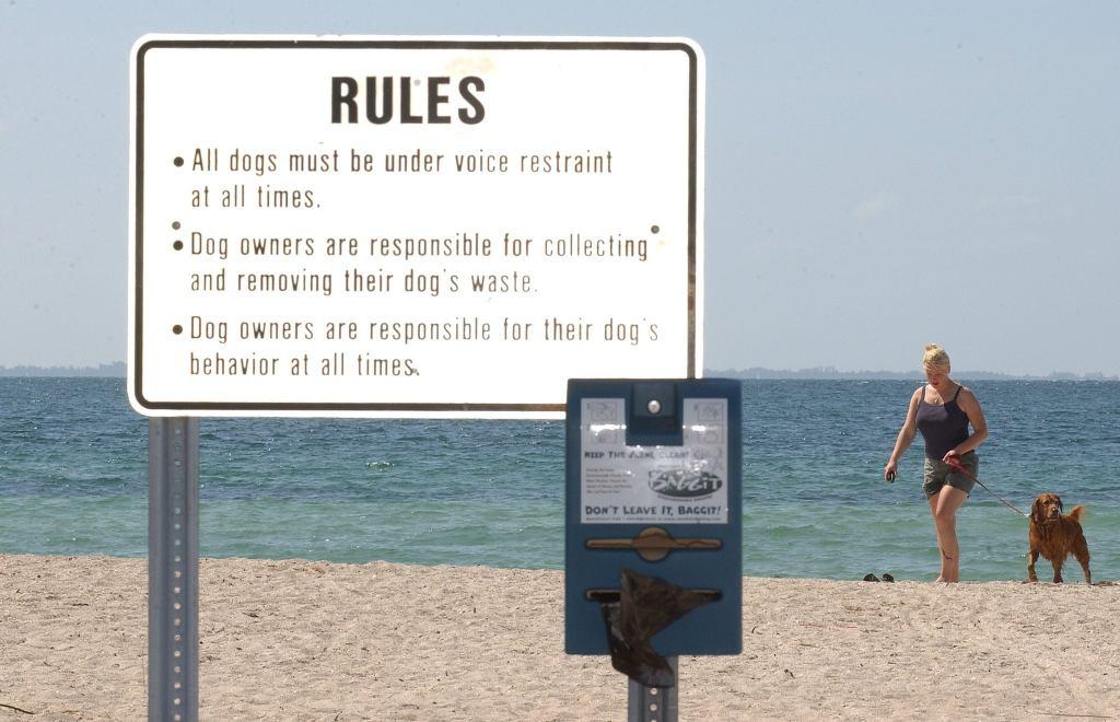a sign at a dog park on the beach