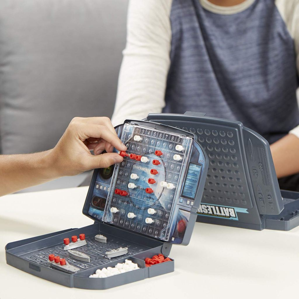 two people playing battleship board game on a table