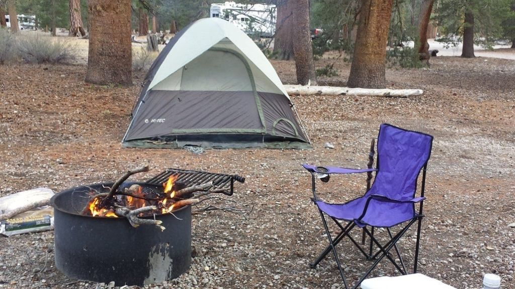 a tent on a forest floor with a camping chair and fire set up