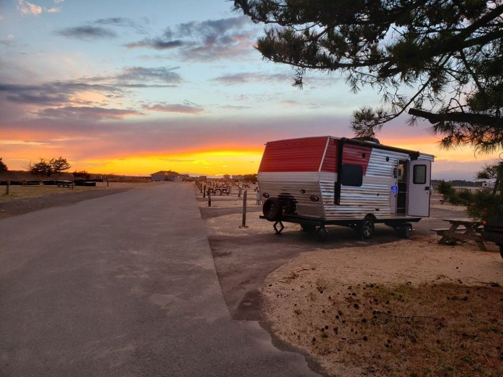 an RV camper sitting in a parking spot at sunset while camping at delaware beach state park