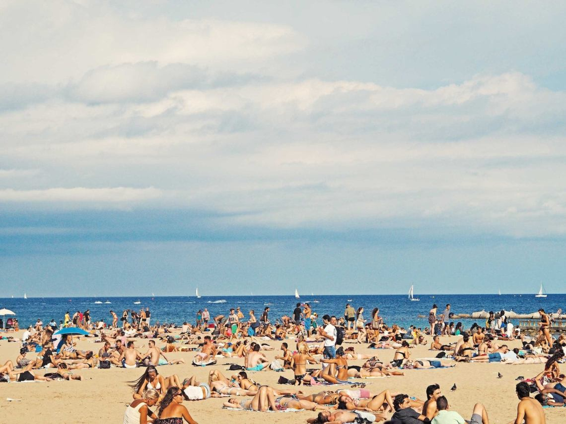Crowd sunbathing on the beach.