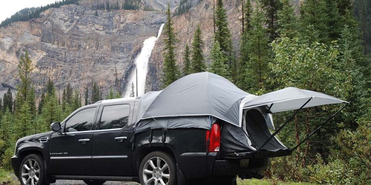 a truck bed tent next to a waterfall outdoors