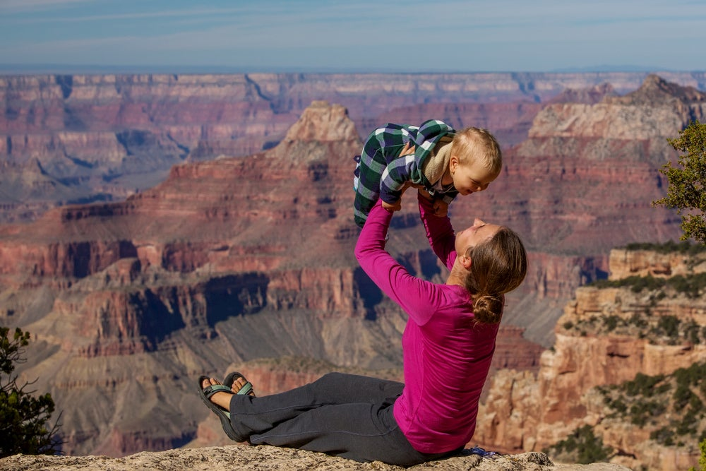Mother lifting her son up in the air with The Grand Canyon in background