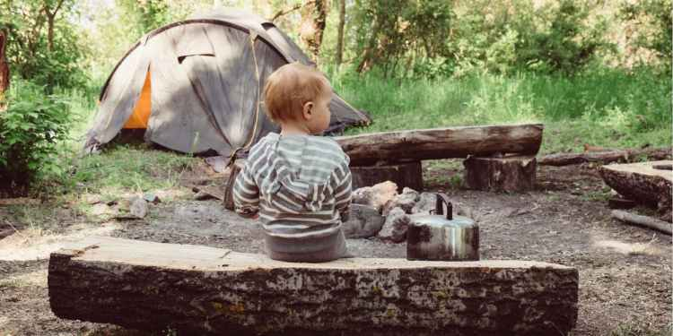 a young boy sitting on a log bench near a campsite