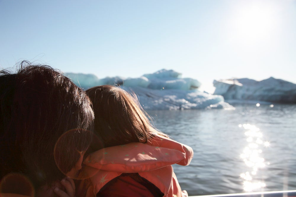 Girl holding on to her father and looking out at glacier in the ocean
