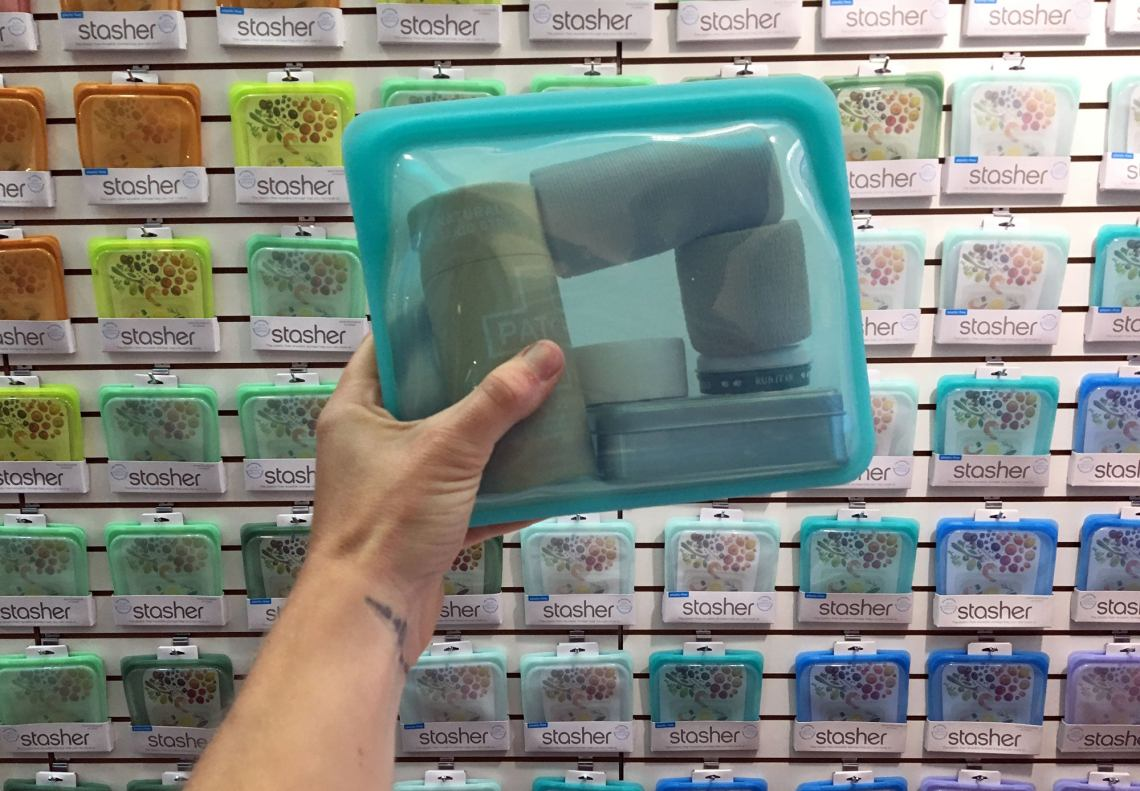 hand holding a full stasher bag in front of product display at outdoor retailer