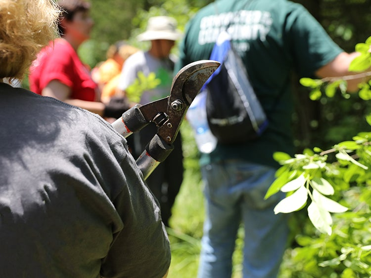 a woman holding plant shears around a group of trail volunteers