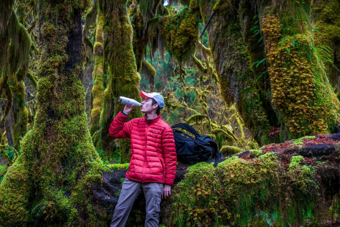 Person drinking Liquid-IV out of a water bottle in the forest.