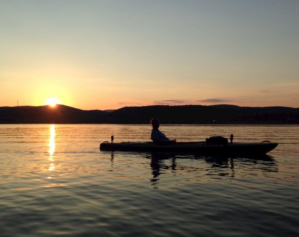 Woman floating on lake at sunset.