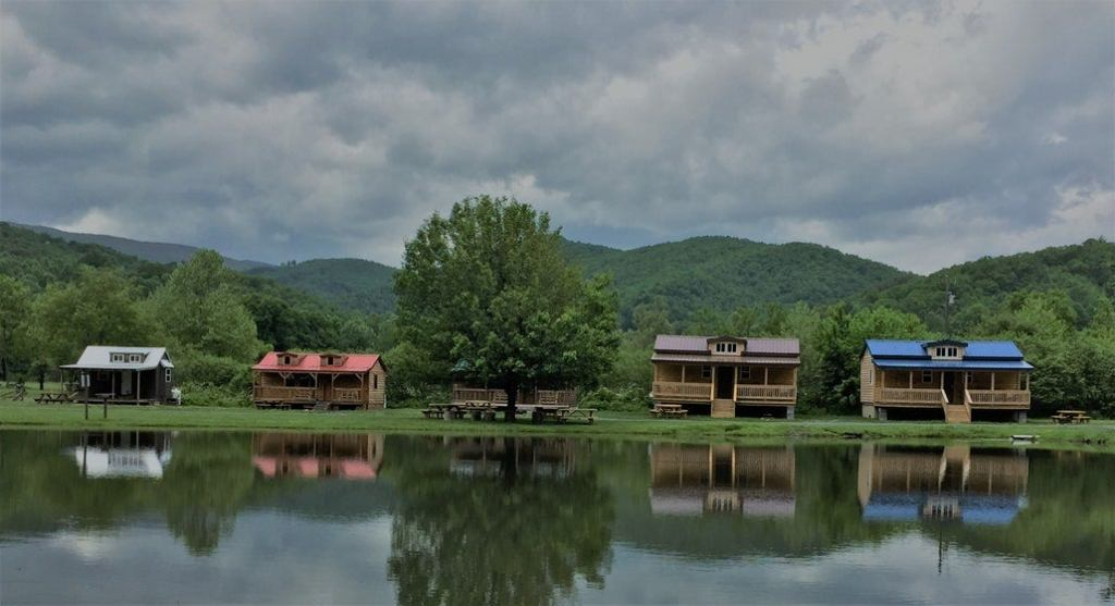 four wood cabins on a lake in the mountains