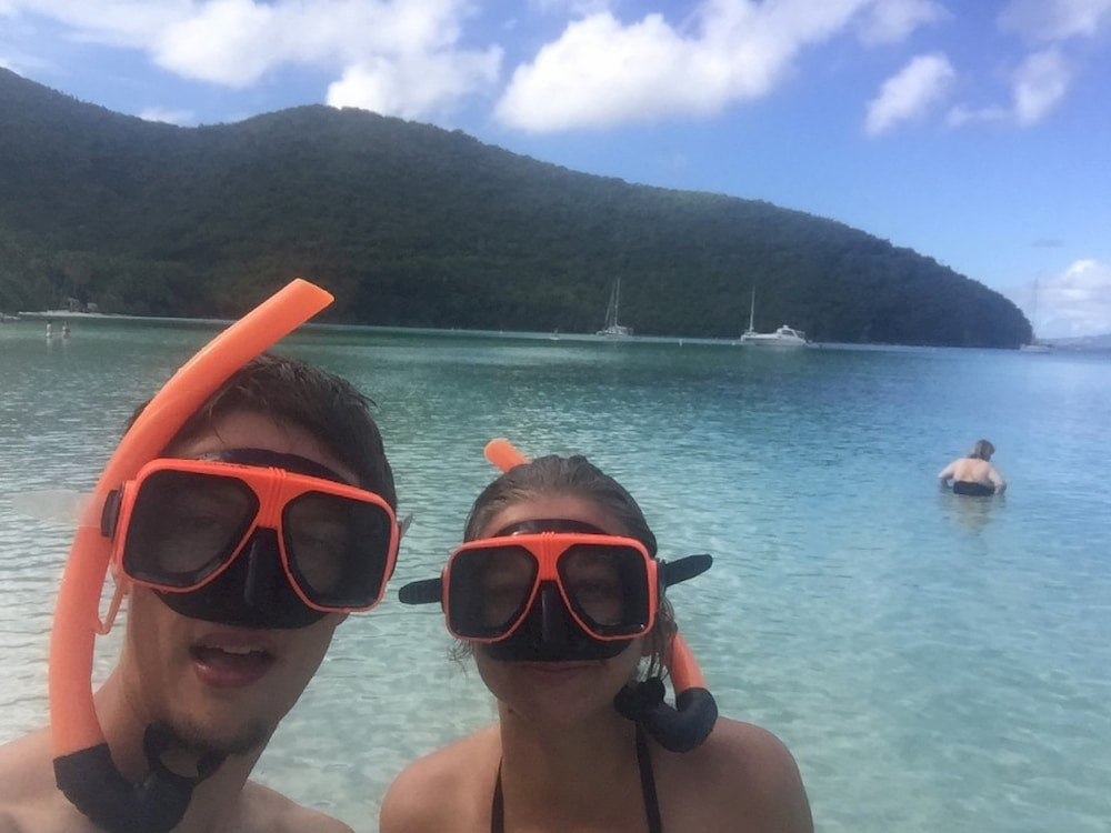 Two people with snorkel gear on.