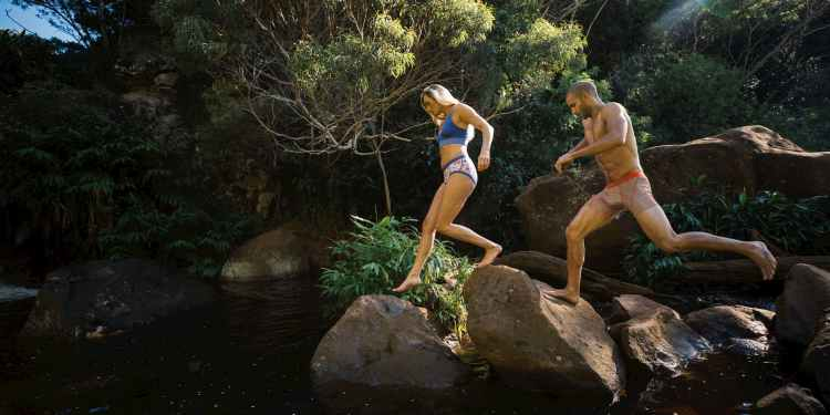 two hikers run on a trail in underwear