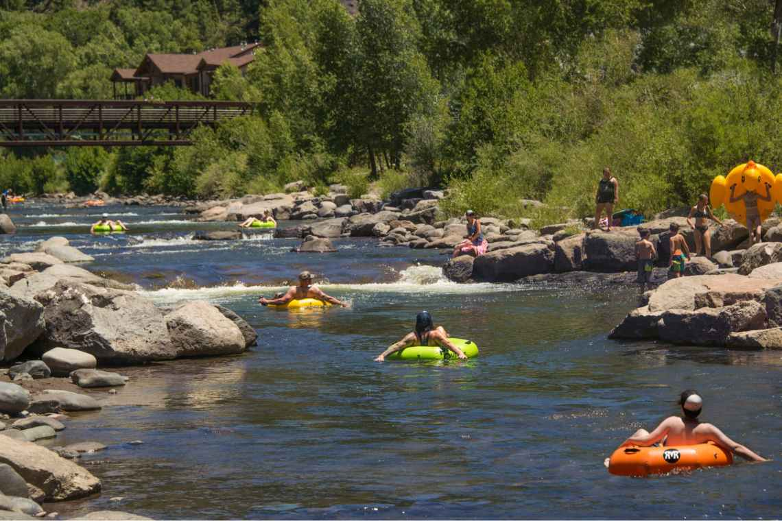 people in colorful river tubes floating on the san juan in colorado