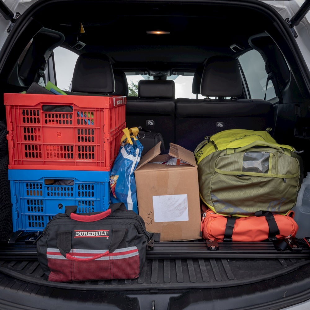 Car packed up with camping bins and a duffel bag.