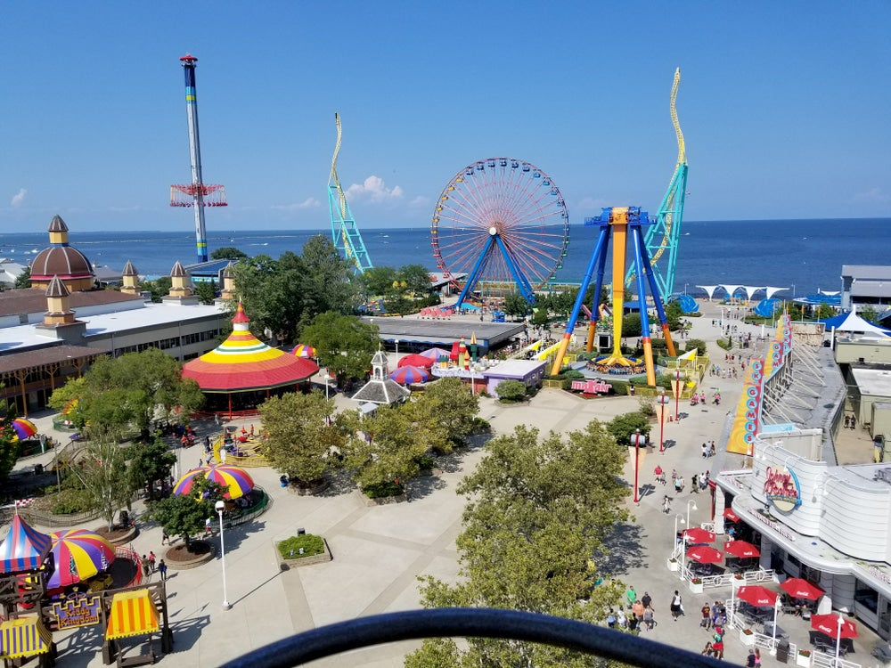Ferris wheel and other rides at amusement park with lake in background