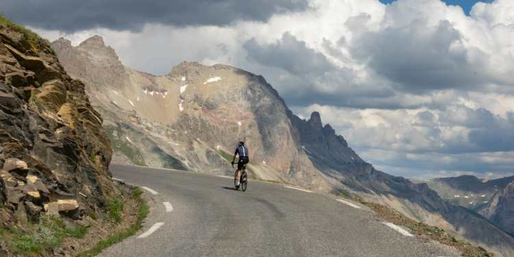 a man riding a bike on a road through mountains