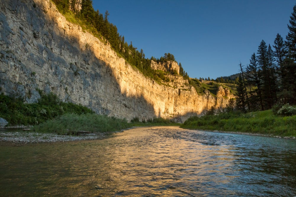 River with cliff wall and sun shining on wall