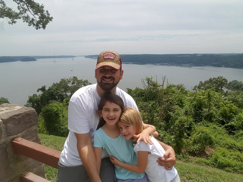 Father and daughters posing with lake and forest in background