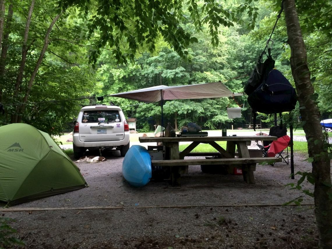 Campsite with tent, umbrella, and kayak,.