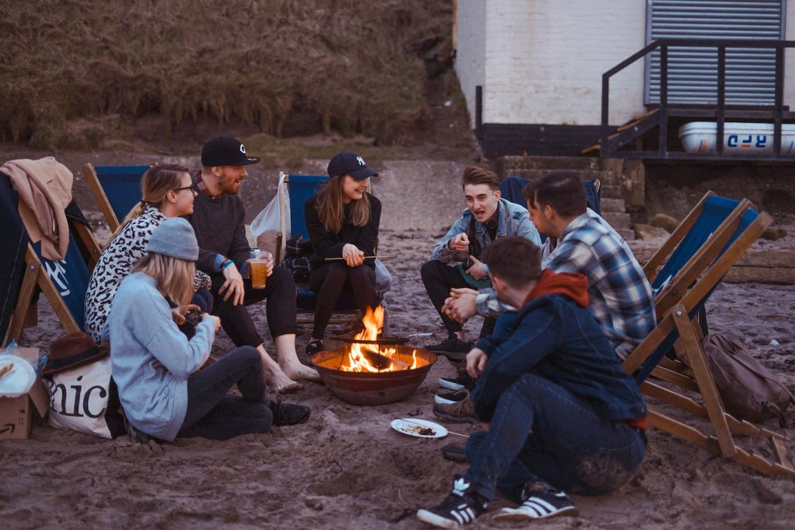 Group of friends drinking beer and hanging out around a fire on the beach.