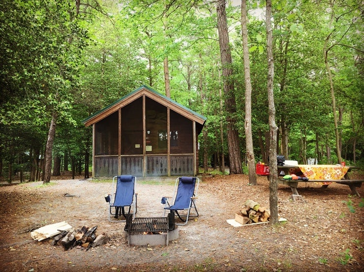 camp chairs set up between camp fire and cabin at Delaware's Trap Pond State Park, photo from a camper on The Dyrt