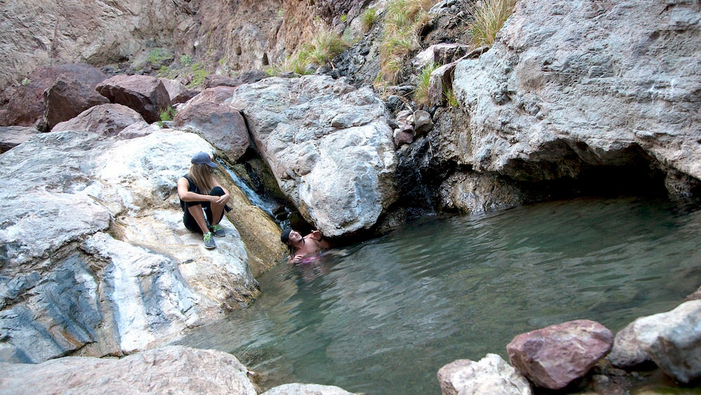 two people in a pool of water in red rocks in nevada