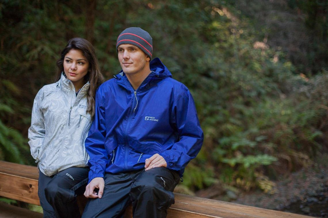 Couple hangs out on bridge in the forest wearing Red Ledge.