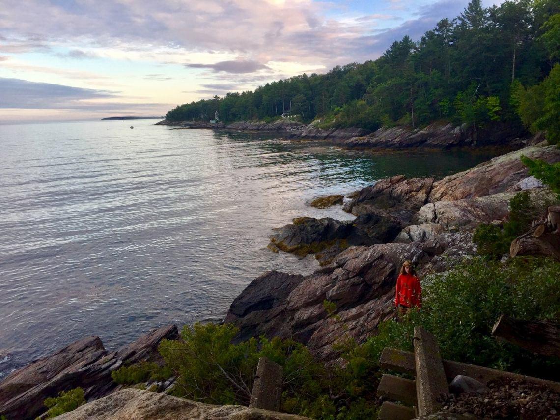 Girl in red jacket walking along coastal cliffs in Maine.