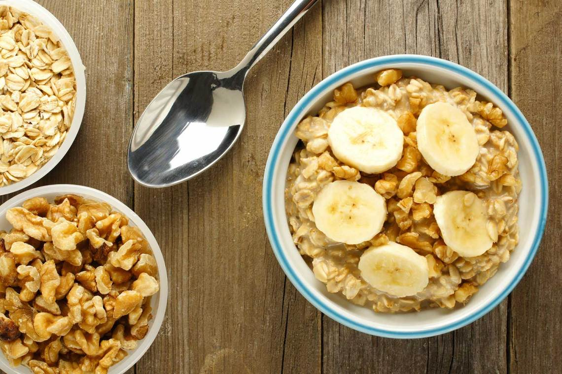 Several bowls filled with granola and banana sit on a wooden table next to a spoon