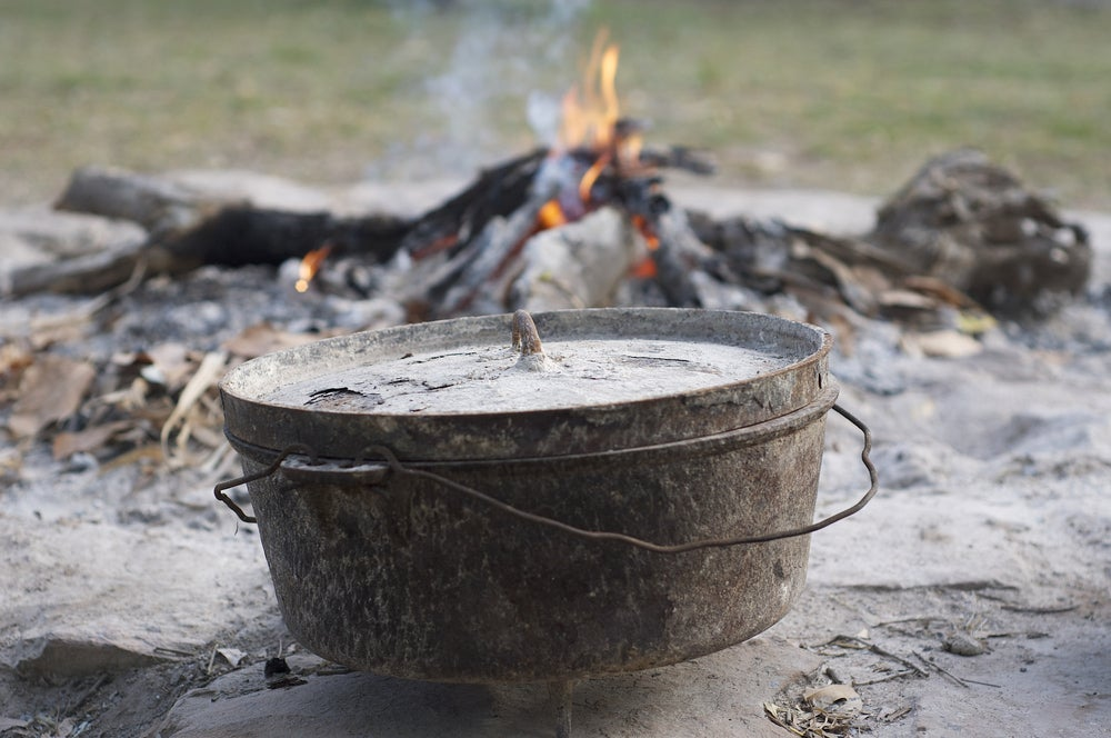 a dutch oven pot near a campfire