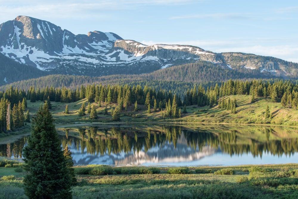 Snowcapped mountain above landscape of Little Molas Lake.