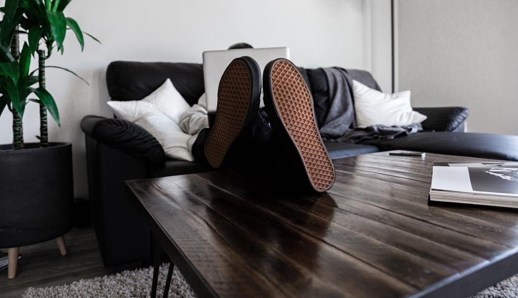 Pessoa sentada no sofá da sua casa, com o pé na mesa de apoio da sala, praticando o home office com tranquilidade.