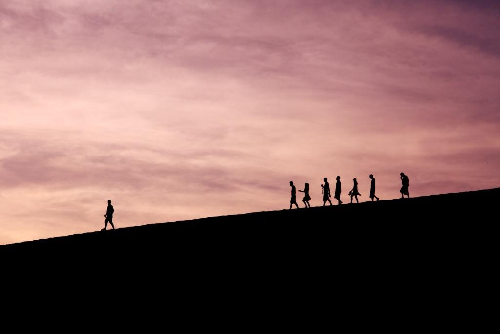 Pessoas seguindo um líder em uma montanha sob um pôr do sol