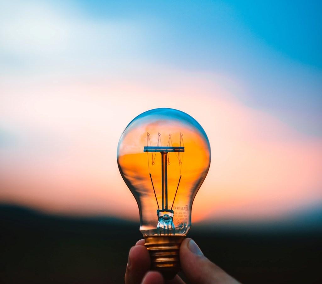 Pessoa segurando uma lâmpada em um pôr do sol, representando que é possível ter um mindset posivito, gerando insights