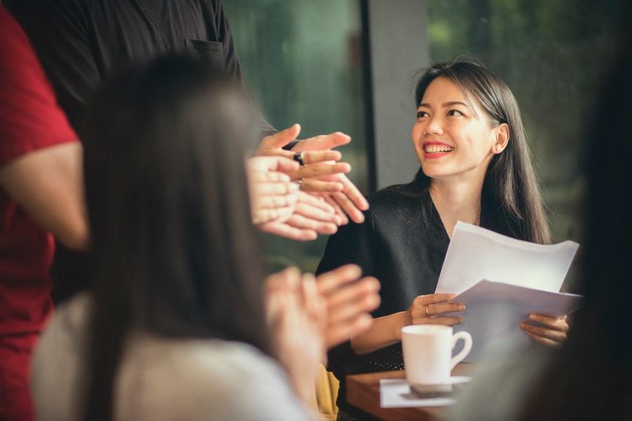 Mulher sorrindo em reunião de equipe.