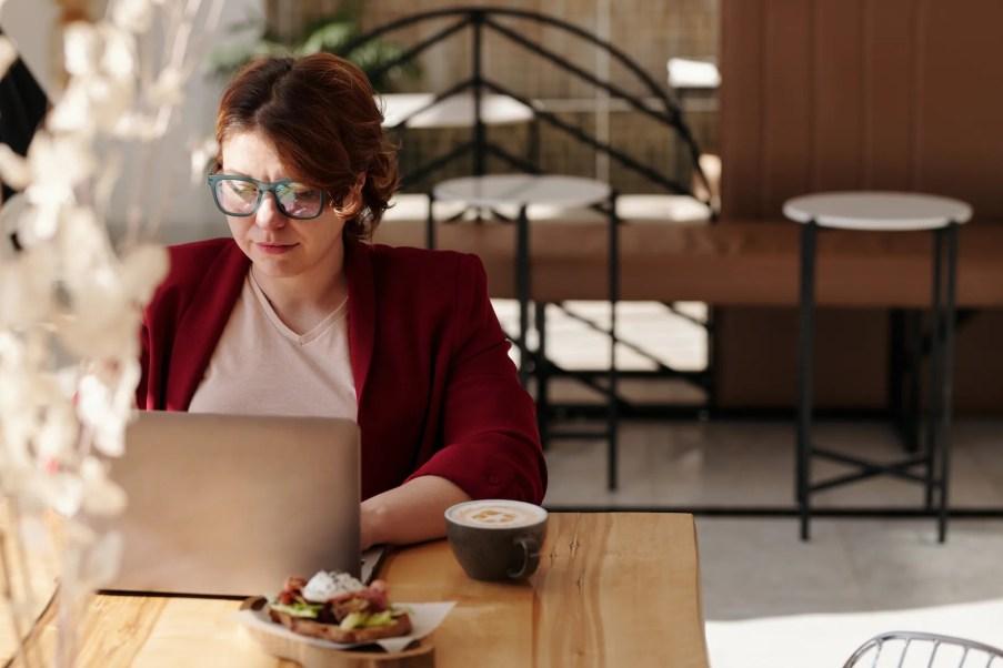 Mulher trabalhando em casa, ao lado xícara de café e um lanche.