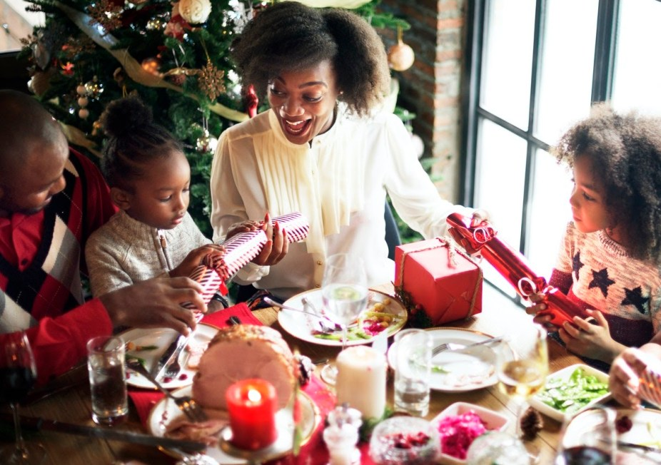 Uma mulher entregando presentes de Natal para sua família.