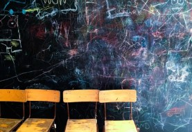 classroom chairs against a blackboard