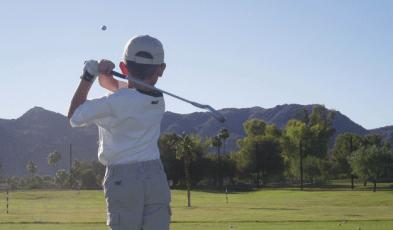 Kid practicing golf iron swing