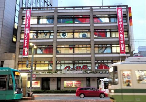 もみじ銀行本店の窓に現れた巨大な「カープ坊や」=11日午後5時46分、広島市中区、上田幸一撮影