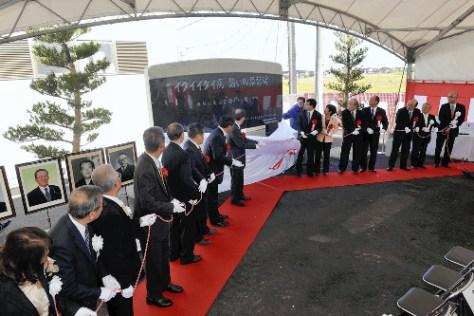 顕彰碑を除幕する関係者ら(12日、富山市で)