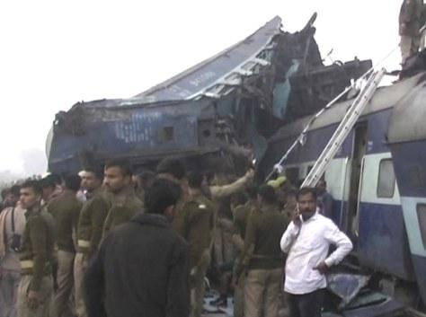 脱線した車両から生存者を助ける救助関係者=インド北部で20日、AP