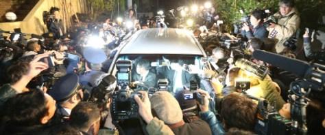 大勢の報道陣に囲まれるASKA容疑者(本名・宮崎重明)を乗せた車=28日夜、東京都目黒区 撮影日:2016年11月28日 | 時事通信社